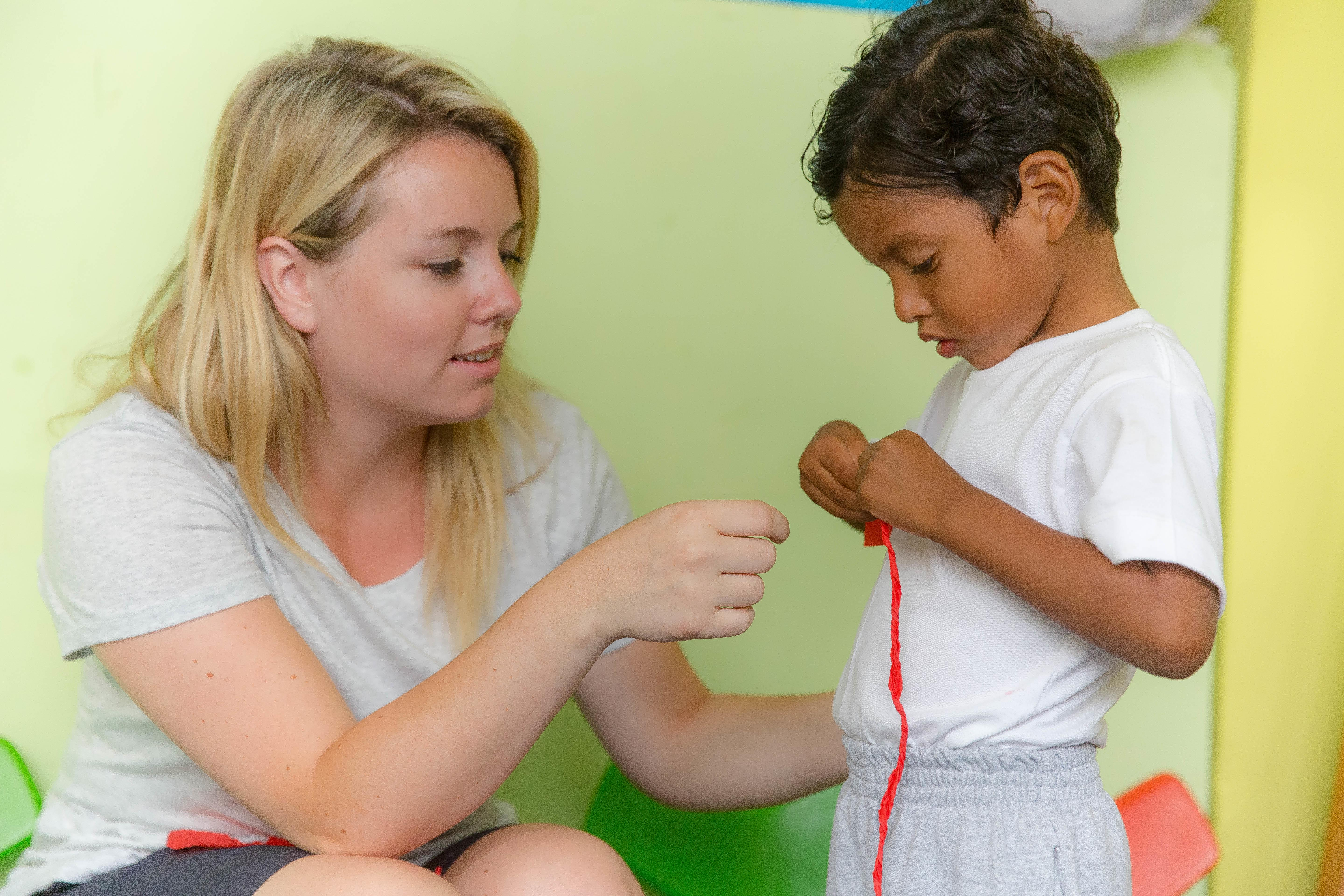 Projects Abroad volunteer working with children in Ecuador helps child with an activity in a day care centre.